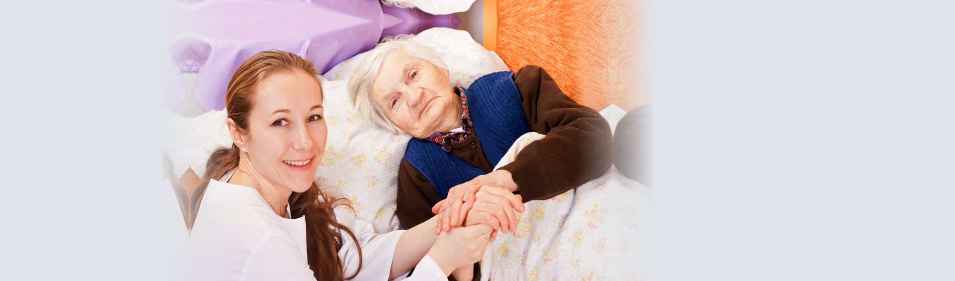 elderly woman in bed holding her caregivers hand