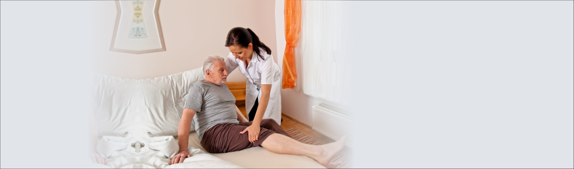 caregiver helping an elderly man from bed