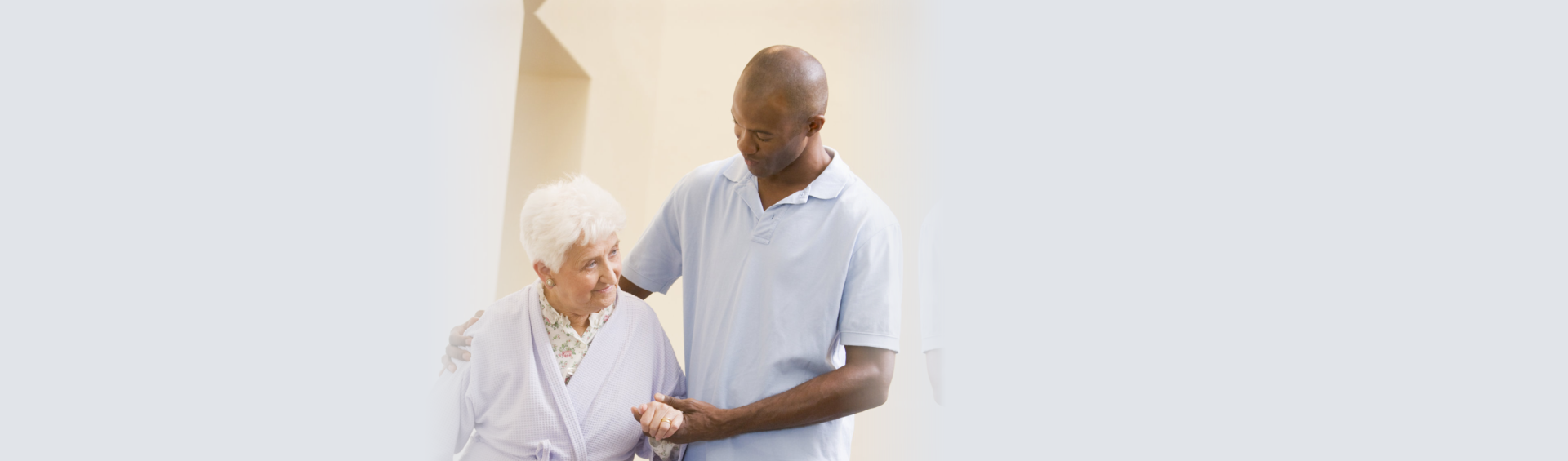 caregiver supporting an elderly woman while walking