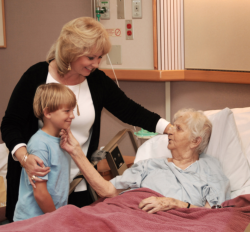 elderly woman in bed with her daugther and grandchild